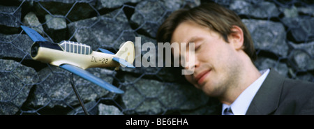 Man with eyes closed, smiling, leaning head against wall, toy airplane in foreground - Stock Photo