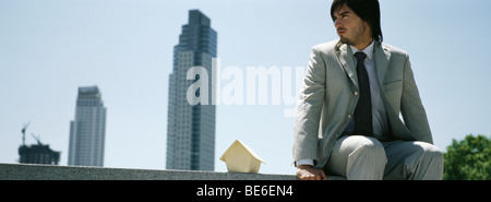Man sitting on ledge beside miniature wooden house, skyscrapers in distance - Stock Photo
