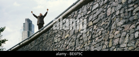 Businessman standing on wall with arms raised, skyscraper in background - Stock Photo
