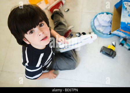Little boy sitting on floor playing with toys, looking up at camera - Stockfoto