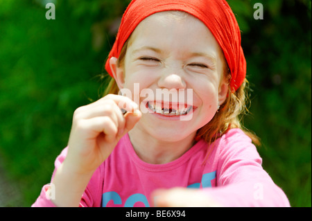 Little girl with a tooth gap, top incisor teeth are missing, happily smiling over the lost tooth for the tooth fairy - Stock Photo