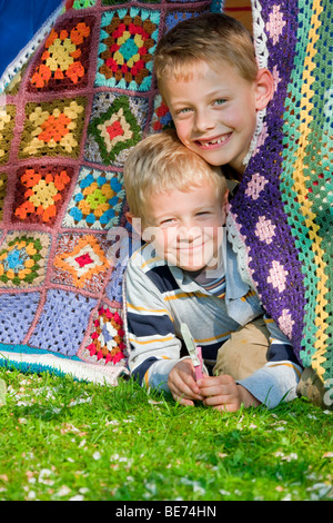 Two boys, 7 and 5, peering out of their tent - Stock Photo