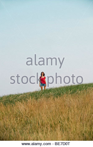 A young woman standing on a hillside - Stock Photo