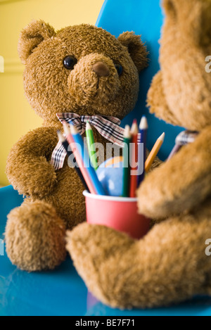 Teddy bears seated face to face with cup of colored pencils between them - Stock Photo