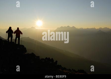 Two Hikers on Glanderspitze looking at Krahberg and Lechtaler Alpen range, Venet, Oetztaler Alpen range, Tyrol, - Stock Photo