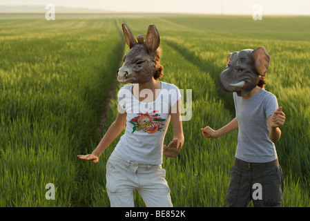 Two females wearing animal masks, dancing in field - Stock Photo