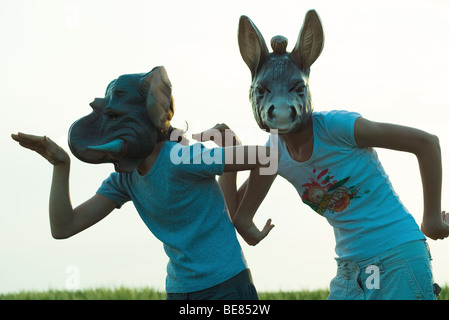 Two females wearing animal masks outdoors, gesturing with arms - Stockfoto