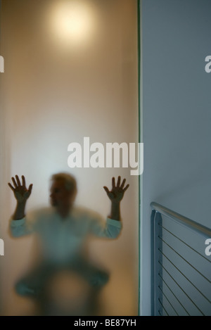 Man crouching behind window, hands pressed against glass - Stock Photo