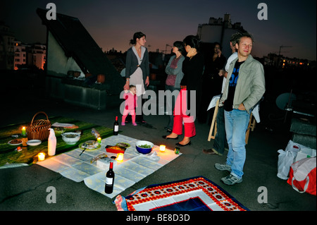 Paris, France - Group French Adults Picnicking on Paris Building Rooftop, Night - Stock Photo