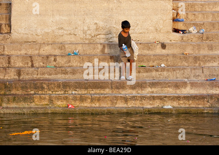 Boy collecting plastic bottles at the Ganges River in Varanasi India - Stock Photo