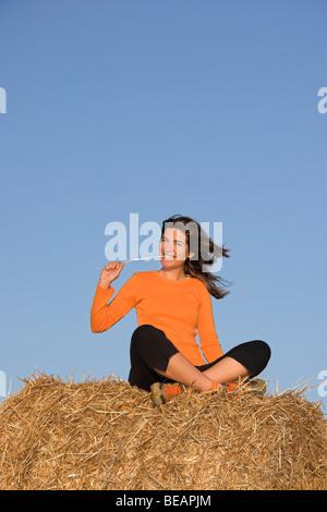 Beautiful woman seated in a field - Stock Photo