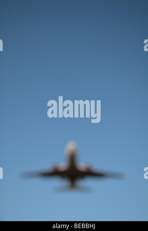 An out of focus image of a plane coming in to land on the South Runway at London's Heathrow Airport, UK. - Stock Photo