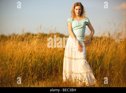 Young woman on a summer field. Red sunset light. - Stock Photo