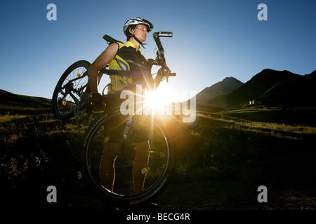 Mountainbiker carrying his bike, Northern Tyrol, Austria, Europe - Stock Photo