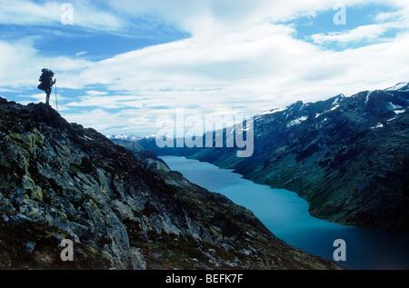 Hiker standing above Gjende (or Gjendin) Lake in the Jotunheimen mountains in Norway's Jotunheimen National Park - Stock Photo