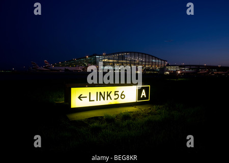 An exterior dusk view Terminal 5 building and a taxiway sign for pilots to navigate around a complicated Heathrow - Stock Photo