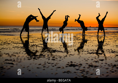 Friends playing on the beach silhouetted against an evening sky. - Stock Photo