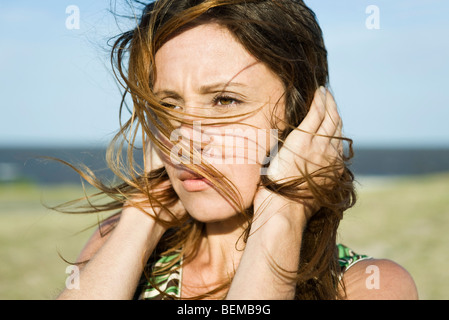 Woman standing in wind, hands holding hair down, close-up - Stock Photo