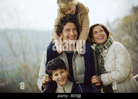 Family together outdoors, father carrying daughter on his shoulders - Stock Photo