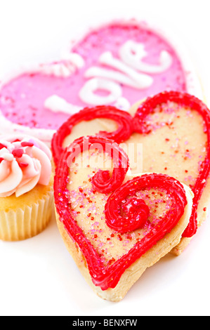 Homemade baked shortbread Valentine cookies and cupcake with icing on white background - Stock Photo