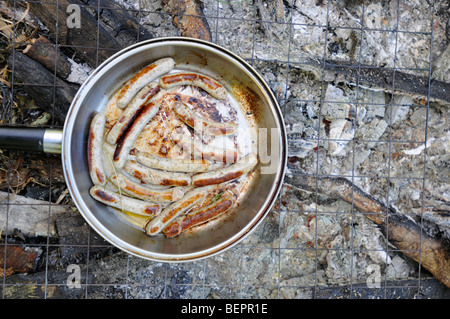 Sausages cooking on a campfire - Stockfoto