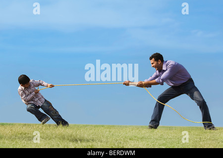 Tug of war between son and father - Stock Photo