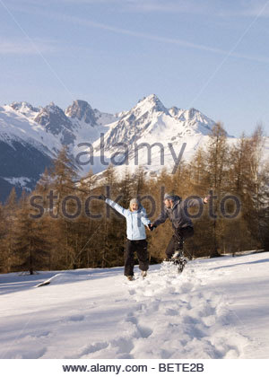 couple jumping in the snow - Stockfoto