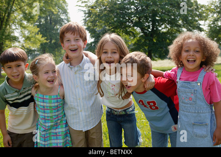 group of six children in the park laughing with their arms around each other - Stock Photo
