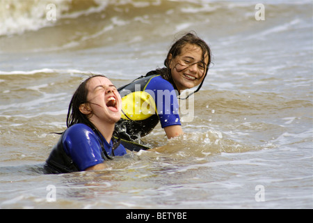 two girls swimming in the sea in wet suits having a great time playing in the waves - Stock Photo