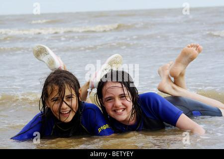 two girls teenagers kids at the beach having fun - Stock Photo