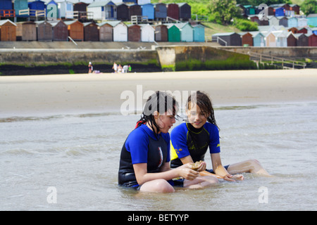 two girls sitting on a sandy beach in wet suits - Stock Photo