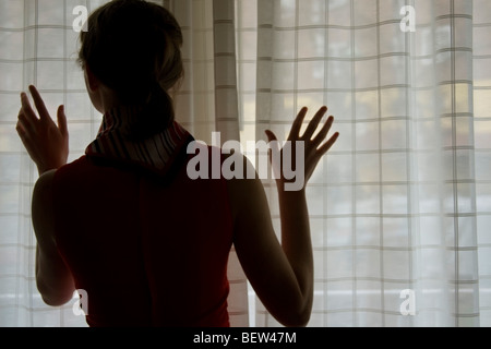 Woman looking out window - Stockfoto