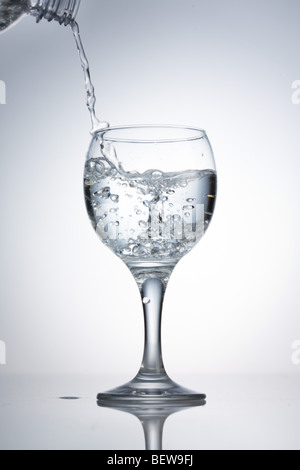 pouring in of water into a glass, close-up - Stockfoto