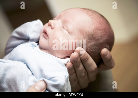 Man holding a sleeping baby in his hands, close-up - Stock Photo