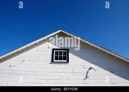 White barn under blue skies - Stock Photo