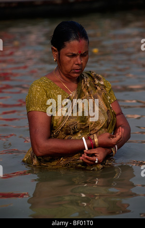 india, allahabad, sangam, woman bathing at the confluence of the rivers ganges and yamuna - Stock Photo