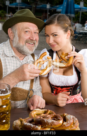 A traditionally clothed German man and woman in a beer garden holding pretzels - Stock Photo