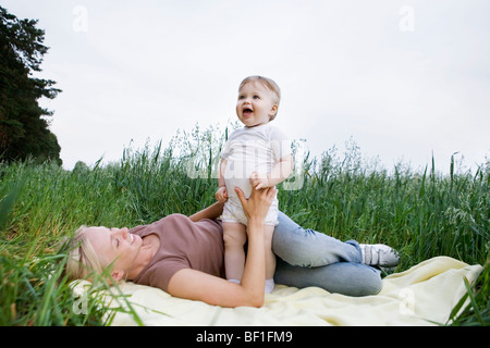 A mother and baby daughter playing on a rug in a field - Stock Photo