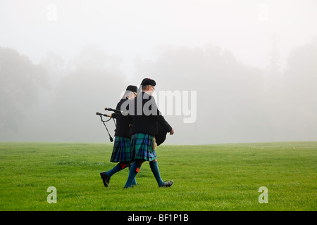Bagpipers in full dress walking through park on a foggy morning. - Stock Photo