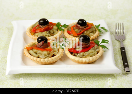 Tartlets with pepper and anchovies. Recipe available. - Stock Photo