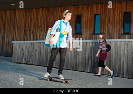 Young man on skateboard with shopping - Stock Photo