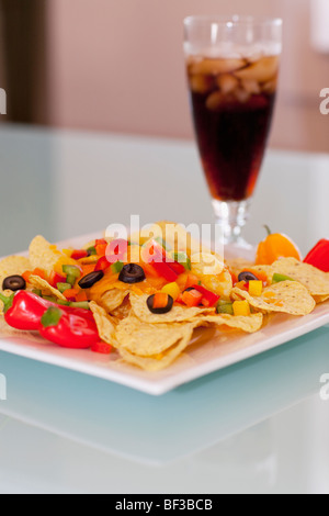 Close-up of chips topped with peppers and olives - Stock Photo