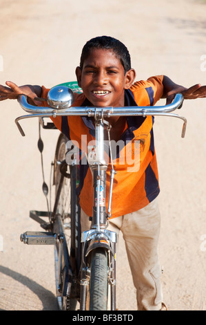 Happy young indian street boy with his bicycle - Stock Photo