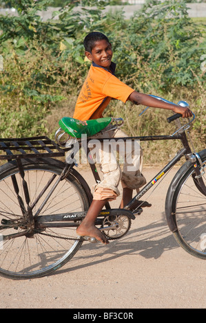 Happy young indian street boy riding a bicycle, Indian style - Stock Photo