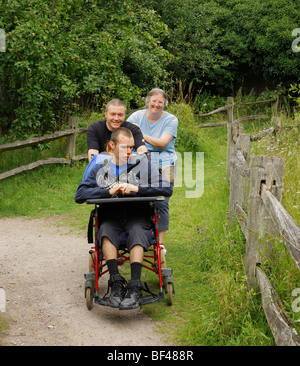 Disabled boy being pushed along by loving parents. - Stockfoto