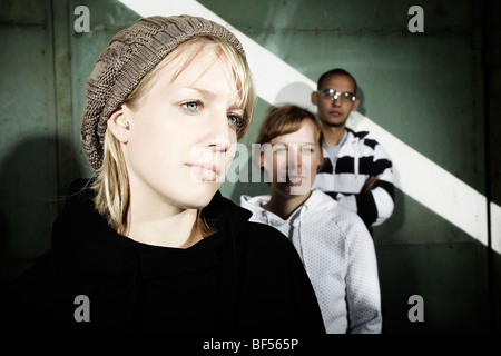 Portrait of a group of youth in front of an old steel gate, in focus a young woman wearing a knitted hat, youth, - Stock Photo