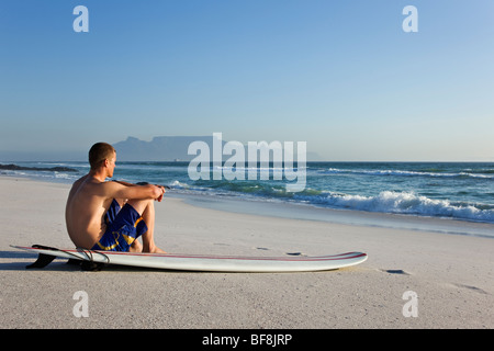 Surfer on Bloubergstrand beach with Table Mountain in background. Cape Town South Africa - Stock Photo