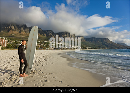 Surfer on camps bay beach with twelve apostles of Table Mountain in background. Cape Town South Africa - Stock Photo