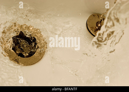 running water down the plug hole - Stock Photo