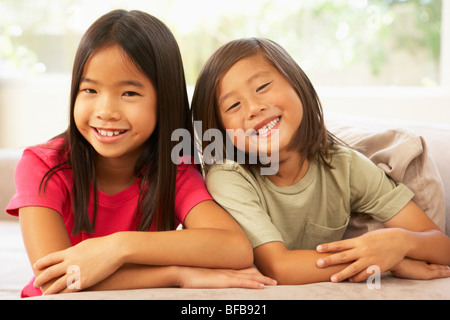 Two Girls Relaxing On Sofa At Home - Stockfoto